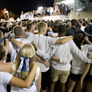 Thousands of students sing the Penn State Alma Mater outside the Old Beaver Stadium at Penn State, in State College, Pa. on Monday, Sept. 8, 2014. The NCAA on Monday lifted the on-the-field sanctions placed on the Penn State football team for the Jerry Sandusky scandal, including immediately eliminating the postseason ban that had two more seasons left and restoring scholarships next season. (AP Photo/John Beale)