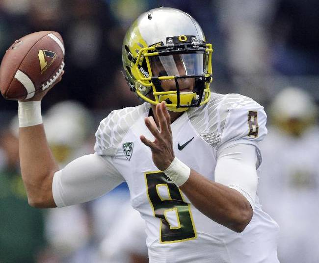 In tihs Oct. 12, 2013, file photo, Oregon quarterback Marcus Mariota throws a pass against Washington in the first half of an NCAA college football game in Seattle.  One of the most notable numbers in Mariota's stat line is 0. That's the number of interceptions he's thrown in the first half of the season