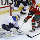 St. Louis Blues goalie Brian Elliott (1) stops a point-blank shot by Minnesota Wild left wing Matt Cooke (24) during the third period of an NHL hockey game in St. Paul, Minn., Thursday, April 10, 2014. Elliott replaced Ryan Miller in the net during the th
