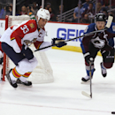 Florida Panthers defenseman Willie Mitchell, front left, pursues the puck with Colorado Avalanche left wing Gabriel Landeskog, right, of Sweden, as Panthers goalie Roberto Luongo watches during the third period of the Panthers' 4-3 overtime win in an NHL
