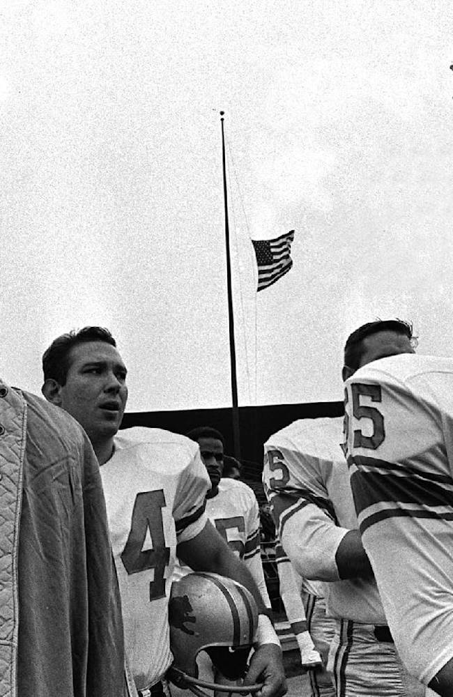In this Nov. 24, 1963, file photo, Detroit Lions' Nick Pietrosante, left, and Wayne Walker (55) stand during ceremonies honoring slain President John F. Kennedy before an NFL football game against the Minnesota Vikings at Metropolitian Stadium in Minneapolis. Americans grieved in front of their televisions on a brutally grim Sunday afternoon 50 years ago as a horse-drawn caisson took the body of President Kennedy to lie in state in the Capitol rotunda. As unimaginable as it might seem today, in seven cities men played football as the NFL went on despite the assassination two days earlier
