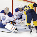 Edmonton Oilers defenseman Andrew Ference (21) blocks a shot by Nashville Predators defenseman Roman Josi (59), of Switzerland, as Oilers goalie Viktor Fasth (35), of Sweden, reaches for the pic in the first period of an NHL hockey game Thursday, Nov. 27,