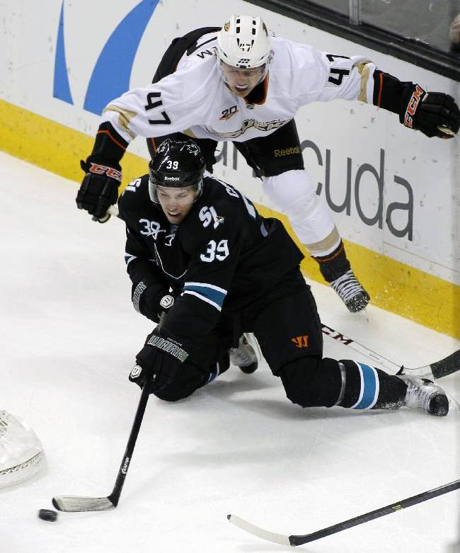 San Jose Sharks' Logan Couture, front, and Anaheim Ducks' Hampus Lindholm struggle for the puck during the first period of an NHL hockey game, Sunday, Dec. 29, 2013, in San Jose, Calif