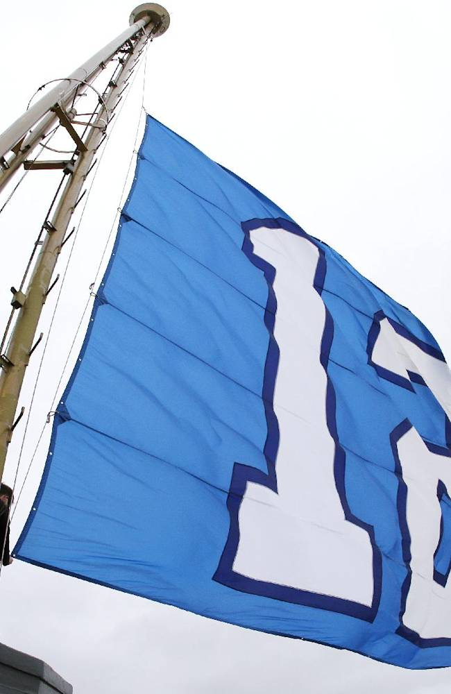 In this photo made with a fisheye lens, Matt Waffle, facilities supervisor at the Space Needle, makes an adjustment to tighten the Seattle Seahawks' 12th Man flag as it flies from the top of the Space Needle, Friday, Jan. 10, 2014, in Seattle. The Seahawks will host the New Orleans Saints in an NFL football second-round playoff game on Saturday