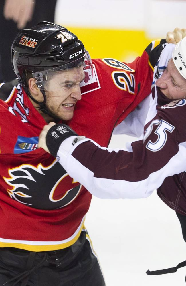 Colorado Avalanche's Cody McLeod, right, fights with Calgary Flames' Lane MacDermid during the first period of an NHL hockey game, Friday, Dec. 6, 2013 in Calgary, Alberta