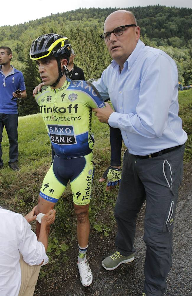 A doctor tends to Spain's Alberto Contador, as team manager Bjarne Riis of Denmark holds Contador after he crashed in the tenth stage of the Tour de France cycling race over 161.5 kilometers (100.4 miles) with start in Mulhouse and finish in La Planche des Belles Filles, France, Monday, July 14, 2014. Contador abandoned the race a bit later in the race