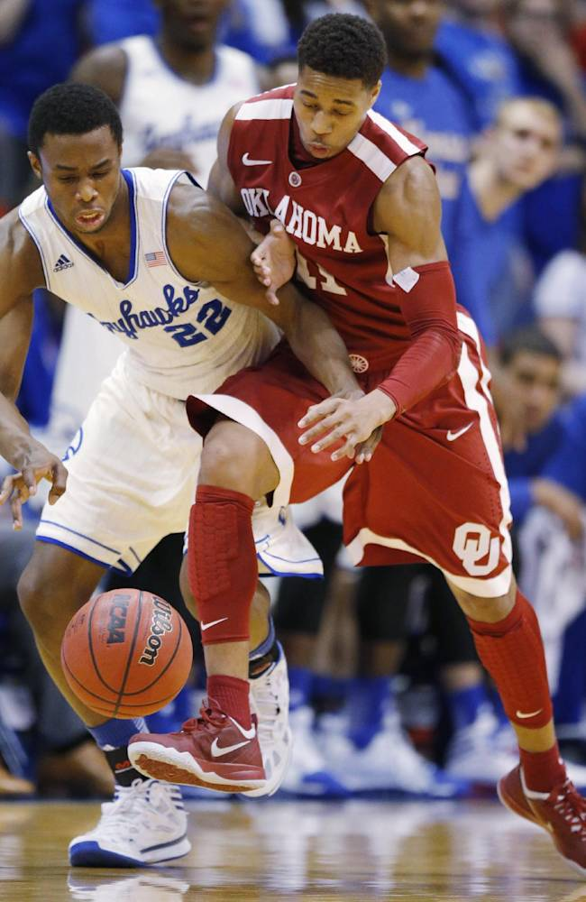 Kansas guard Andrew Wiggins (22) and Oklahoma guard Isaiah Cousins (11) chase down a loose ball during the second half of an NCAA college basketball game in Lawrence, Kan., Monday, Feb. 24, 2014. Kansas defeated Oklahoma 83-75