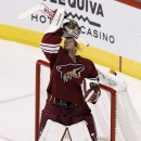 Arizona Coyotes' Mike Smith puts his mask back on during the second period of an NHL hockey game against the St. Louis Blues on Saturday, Oct. 18, 2014, in Glendale, Ariz The Associated Press