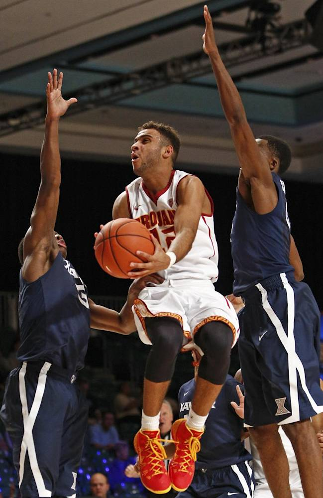 Southern California's Julian Jacobs, center, goes up for the basket as Xavier's Brandon Randolph, left, and Semaj Christon defend during the second half of an NCAA college basketball game in Paradise Island, Bahamas, Saturday, Nov. 30, 2013. USC won 84-78