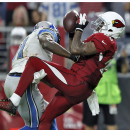 Arizona Cardinals free safety Rashad Johnson, right, intercepts a pass as Detroit Lions wide receiver Calvin Johnson makes the hit during the second half of an NFL football game, Sunday, Nov. 16, 2014, in Glendale, Ariz The Associated Press