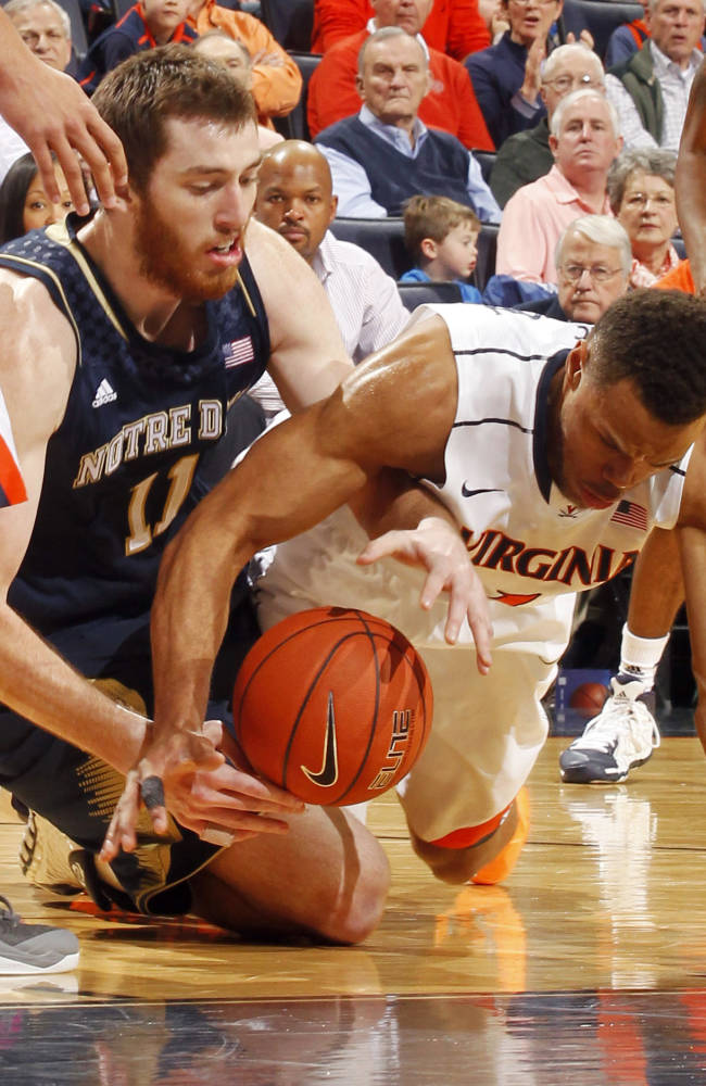 Notre Dame center Garrick Sherman (11) goes after a loose ball with Virginia guard Justin Anderson during an NCAA college basketball game Saturday, Feb. 22, 2014, in Charlottesville, Va