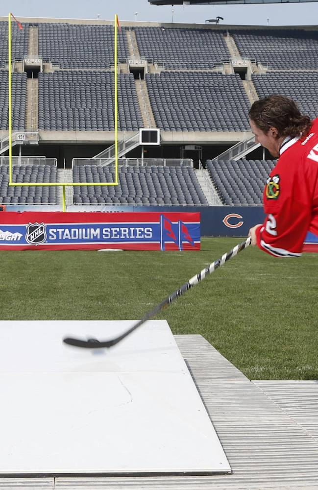Chicago Blackhawks' Duncan Keith shoots a puck from the 40-yard line, 150 feet from the goal post, at Soldier Field as part of a promotion for the Stadium Series hockey game between the Blackhawks and Pittsburgh Penguins next March, Thursday, Sept. 19, 2013, in Chicago