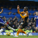 Chelsea's Gary Cahill, left puts up a foot as he tackles Hull's Sone Aluko for which he was shown a yellow card by referee Chris Foy, during their English Premier League soccer match between Chelsea and Hull City at Stamford Bridge stadium in London, Satu