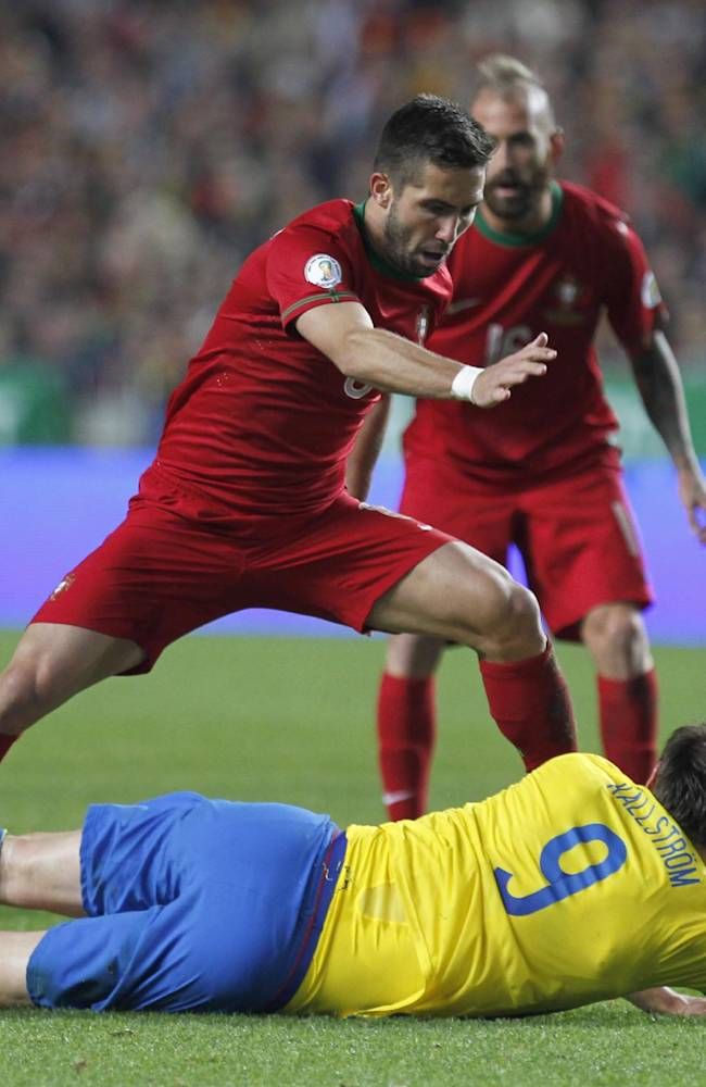 Portugal's Joao Moutinho, top, clashes with Sweden's Kim Kallstrom during a World Cup qualifying first leg playoff soccer match between Portugal and Sweden at the Luz stadium in Lisbon, Portugal, Friday, Nov. 15, 2013. Portugal won 1-0