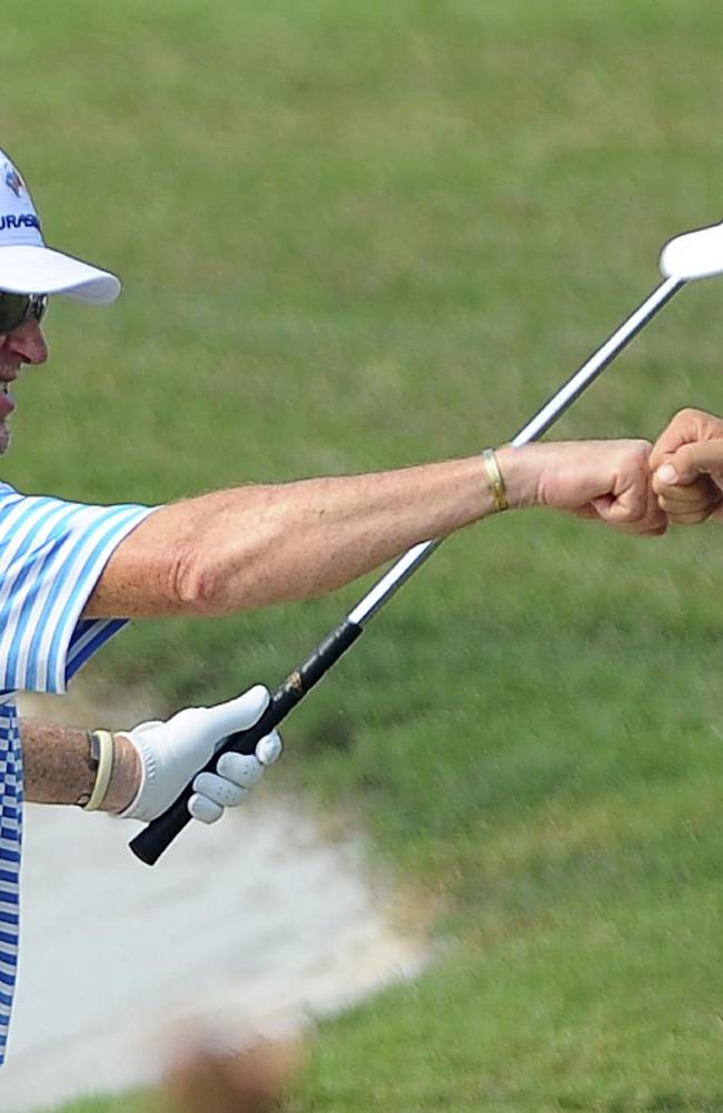 Miguel Angel Jimenez of Spain, left, fist-bumps his caddy after his shot on the third hole during the second round of the EurAsia Cup golf tournament at the Glenmarie Golf and Country Club in Subang, Malaysia, Friday, March 28, 2014