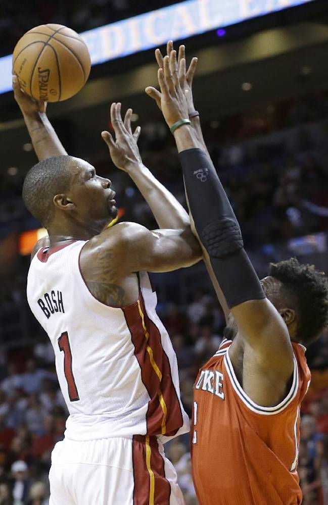 Miami Heat center Chris Bosh (1) shoots against Milwaukee Bucks forward Jeff Adrien during the first half of an NBA basketball game on Wednesday, April 2, 2014, in Miami