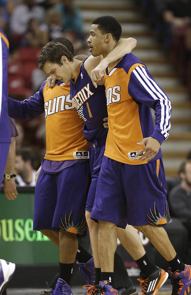 Phoenix Suns guard Goran Dragic, of Slovenia, center, is helped off the court after injuring his ankle during the third quarter of an NBA preseason basketball game in Sacramento, Calif., Thursday, Oct. 17, 2013. Dragic was taken to the locker room and did not return to the game as the Kings went on to won 107-90