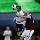 Manchester United's Wayne Rooney, left, competes with West Ham United's James Collins during their English Premier League soccer match at Upton Park, London, Saturday, March 22, 2014