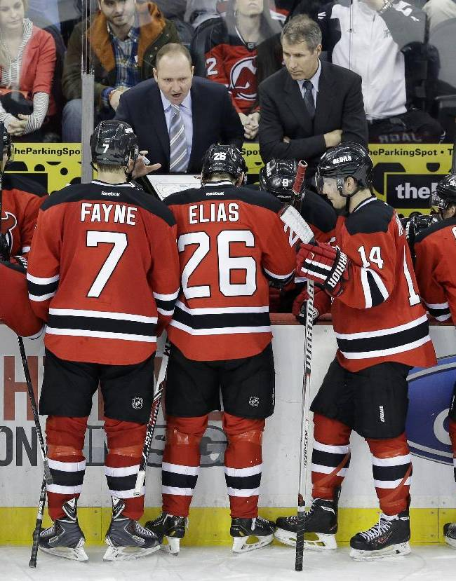 New Jersey Devils head coach Peter DeBoer, center left, talks strategy with his players during the third period of an NHL hockey game against the Toronto Maple Leafs Sunday, March 23, 2014, in Newark, N.J. The Devils won 3-2