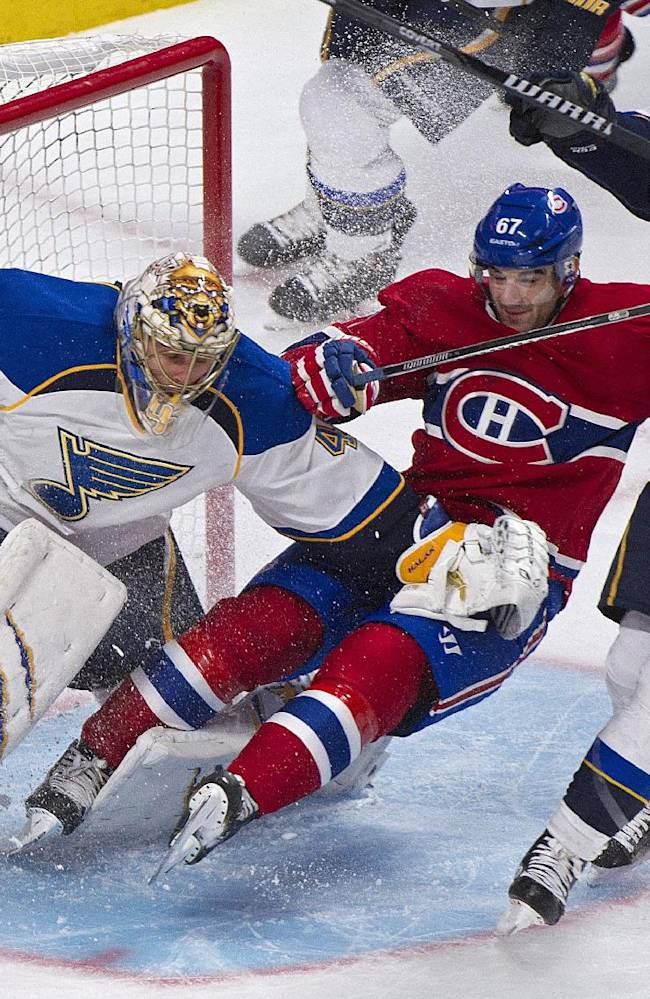 Montreal Canadiens' Max Pacioretty, center, slides in on St. Louis Blues goaltender Jaroslav Halak as Blues' Chris Stewart, right, defends during the first period of an NHL hockey game in Montreal, Tuesday, Nov. 5, 2013