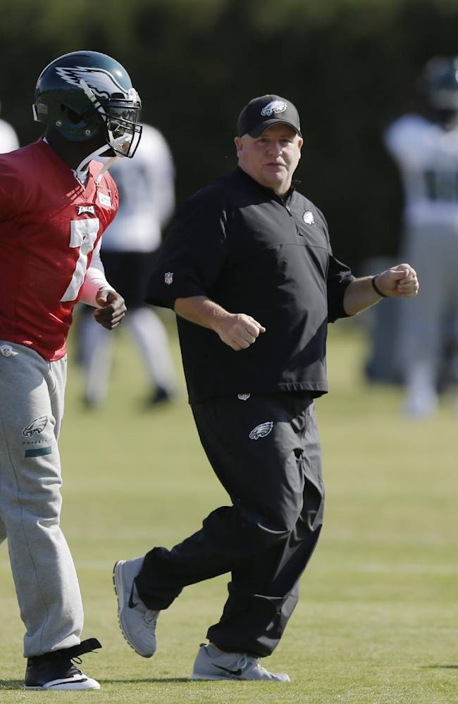 Philadelphia Eagles quarterback Michael Vick runs with head coach Chip Kelly during practice at the NFL football team's training facility, Tuesday, Oct. 29, 2013, in Philadelphia