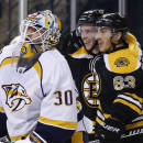 Boston Bruins left wing Brad Marchand (63) celebrates his goal with teammate Reilly Smith as Nashville Predators goalie Carter Hutton (30) looks on during the second period of an NHL hockey game in Boston, Tuesday, Dec. 23, 2014. (AP Photo/Elise Amendola)