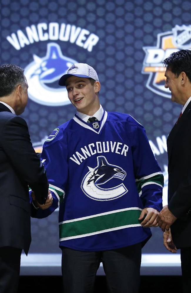 Jake Virtanen shakes hands with Vancouver Canucks officials after being chosen sixth overall during the first round of the NHL hockey draft, Friday, June 27, 2014, in Philadelphia
