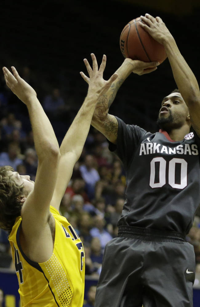 Arkansas guard Rashad Madden (00) shoots over California's Ricky Kreklow, left, in the first half of an NCAA college basketball game in the NIT tournament Monday, March 24, 2014, in Berkeley, Calif. (AP