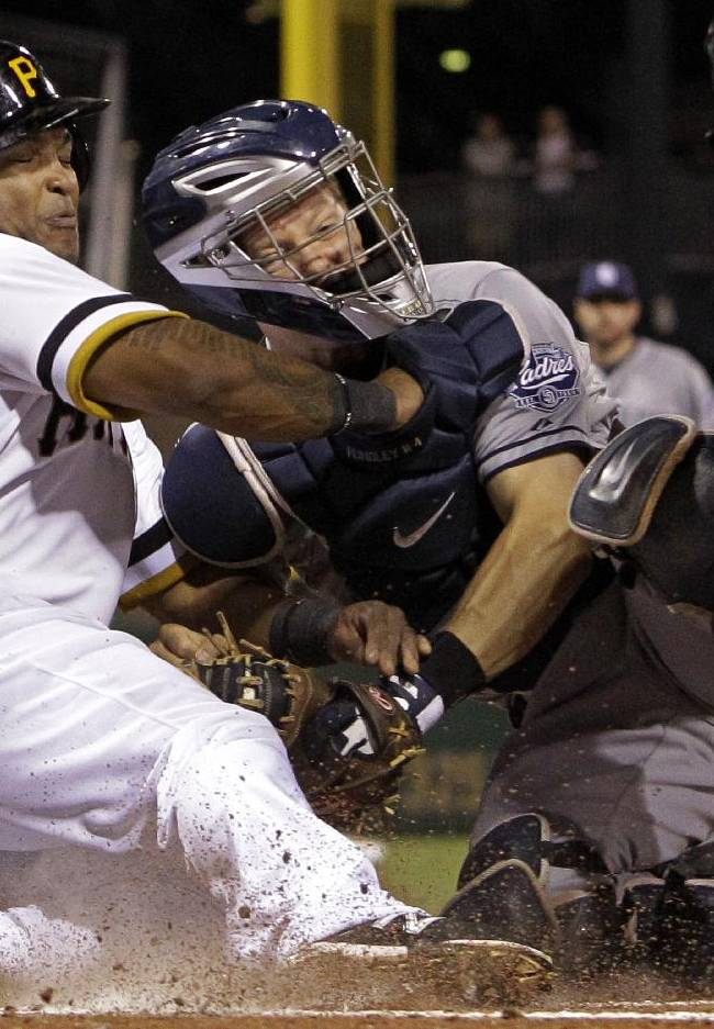 Pittsburgh Pirates' Marlon Byrd, left, is tagged out by San Diego Padres catcher Nick Hundley while trying to score during the third inning of a baseball game Tuesday, Sept. 17, 2013, in Pittsburgh