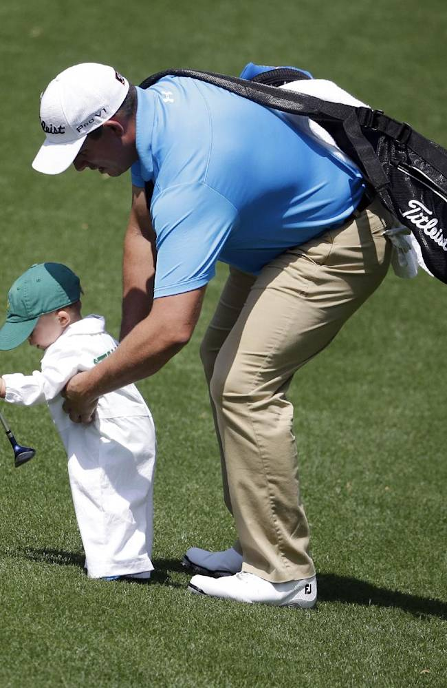 Scott Stallings picks up his son Finn during the par three competition at the Masters golf tournament Wednesday, April 9, 2014, in Augusta, Ga