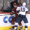Phoenix Coyotes' Shane Doan, left, is checked into the boards by St Louis Blues' Jay Bouwmeester (19) during the second period of an NHL hockey game on Sunday, March 2, 2014, in Glendale, Ariz The Associated Press
