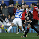 Queens Park Rangers' Charlie Austin, left, takes the ball past Manchester United's Phil Jones during the English Premier League soccer match between QPR and Manchester United at Loftus Road stadium in London, Saturday, Jan. 17, 2015