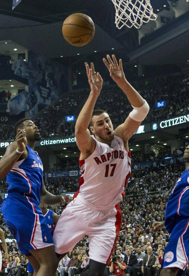 Toronto Raptors' Jonas Valanciunas, center, looses control of the ball after being fouled by Los Angeles Clippers DeAndre Jordan, left, as Clippers' Jamal Crawford looks on during the first half of an NBA basketball game, Saturday, Jan. 25, 2014 in Toronto