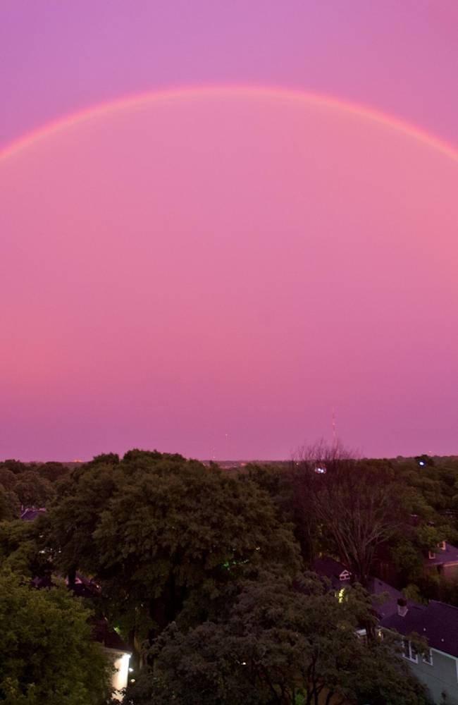 The sky turns pink as a rainbow appears at dusk after a thunderstorm, Thursday, June 5, 2014, in Atlanta