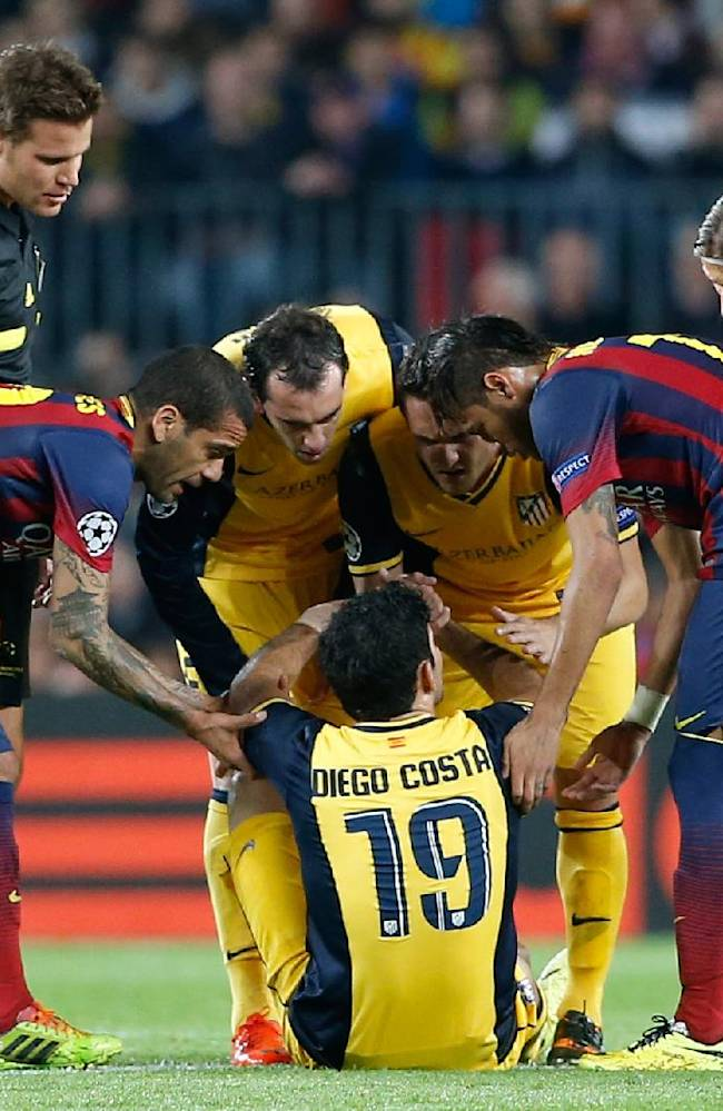 Players check on Atletico's Diego Costa, center, after he injured himself during a first leg quarterfinal Champions League soccer match between Barcelona and Atletico Madrid at the Camp Nou stadium in Barcelona, Spain, Tuesday April 1, 2014