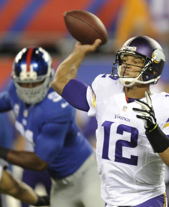 In this Oct. 21, 2013 file photo, Minnesota Vikings quarterback Josh Freeman (12) throws a pass during the first half of an NFL football game against the New York Giants, in East Rutherford, N.J. Freeman signed with the Giants on Monday, April 21, 2014,  to be a backup quarterback to Eli Manning.  Freeman was released by Tampa Bay early last season and spent the rest of 2013 with Minnesota