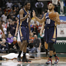 New Orleans Pelicans' Al-Farouq Aminu (0) and Eric Gordon (10) celebrate Aminu's steal from Milwaukee Bucks' Khris Middleton, on ground, in the closing seconds of an NBA basketball game Wednesday, Feb. 12, 2014, in Milwaukee. New Orleans won 102-98 The As