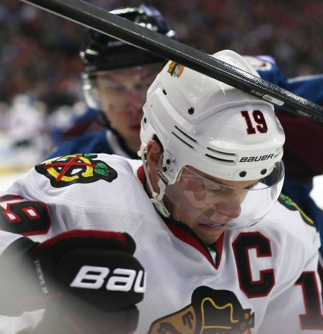 Chicago Blackhawks center Jonathan Toews, front, takes a stick to the helmet from Colorado Avalanche defenseman Erik Johnson while fighting for control of the puck in a corner in the second period of an NHL hockey game in Denver on Wednesday, March 12, 2014