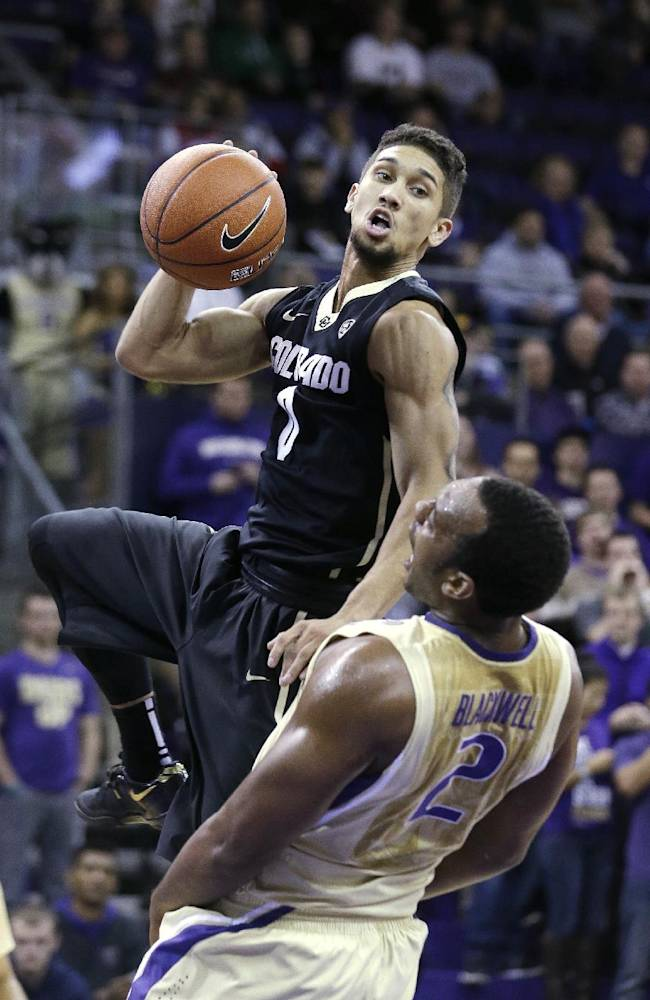 Colorado's Askia Booker (0) crashes into Washington's Perris Blackwell whille shooting in the first half of an NCAA college basketball game on Sunday, Jan. 12, 2014, in Seattle