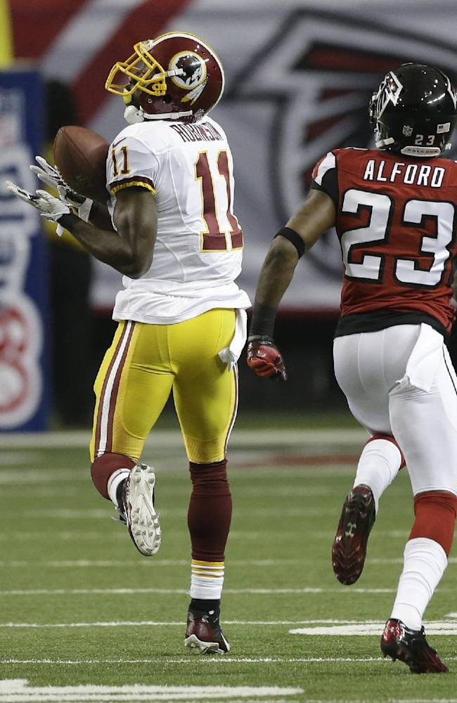 Washington Redskins wide receiver Aldrick Robinson (11) makes a catch against Atlanta Falcons cornerback Robert Alford (23) during the first half of an NFL football game, Sunday, Dec. 15, 2013, in Atlanta