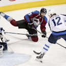 Colorado Avalanche's Maxime Talbot (25) makes a pass between the legs of Winnipeg Jets' Olli Jokinen (12) during the first period of an NHL hockey game on Monday, March 10, 2014 in Denver The Associated Press
