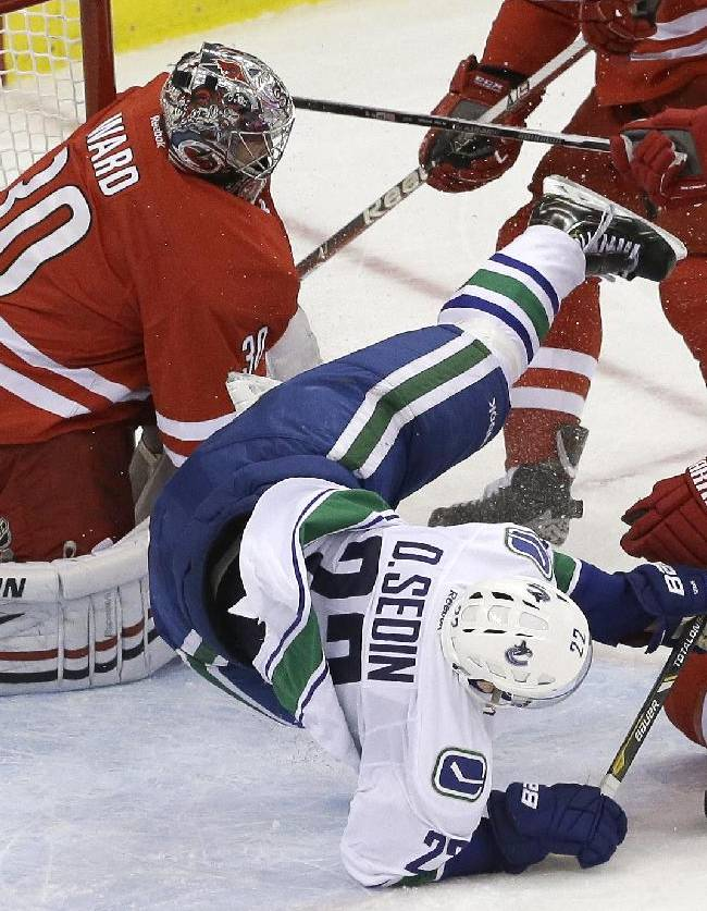 Carolina Hurricanes goalie Cam Ward (30) and Ron Hainsey (65) defend as Vancouver Canucks' Daniel Sedin, of Sweden, is upended during the third period of an NHL hockey game in Raleigh, N.C., Sunday, Dec. 1, 2013. Vancouver won 3-2