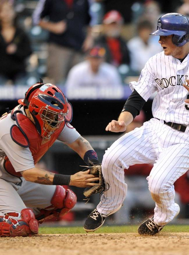 St. Louis Cardinals catcher Tony Cruz tags Colorado Rockies' DJ LeMahieu at home plate without the ball during the 15th inning of a baseball game Thursday, Sept. 19, 2013, in Denver. The Rockies won 7-6 in 15 innings