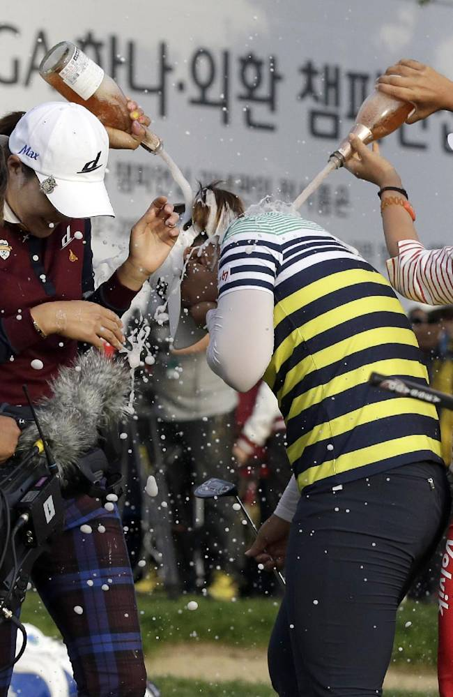 Amy Yang, center, of South Korea is sprayed with champagne by Chella Choi of South Korea, right, after winning the KEB Hana Bank Championship golf tournament at Sky72 Golf Club in Incheon, west of Seoul, South Korea, Sunday, Oct. 20, 2013