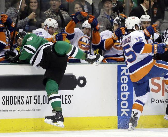 Dallas Stars' Sergei Gonchar (55), of Russia, stops himself from falling into the visitors bench after a collision with New York Islanders' Cal Clutterbuck (15) in the second period of an NHL hockey game, Sunday, Jan. 12, 2014, in Dallas