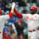 Philadelphia Phillies Ryan Howard, right, high-fives teammate Cody Asche after Howard scored against the Chicago Cubs during the ninth inning of a baseball game on Friday, April 4, 2014, in Chicago The Associated Press