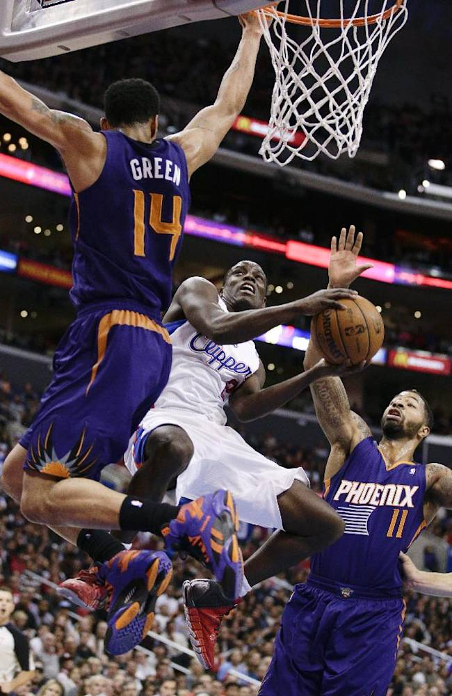 Los Angeles Clippers' Darren Collison, center, goes up for a basket against Phoenix Suns' Gerald Green, left, and Markieff Morris during the first half of an NBA basketball game on Monday, Dec. 30, 2013, in Los Angeles