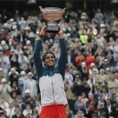 Spain's Rafael Nadal holds the trophy after winning against compatriot David Ferrer in three sets 6-3, 6-2, 6-3, in the final of the French Open tennis tournament, at Roland Garros stadium in Paris, Sunday June 9, 2013. (AP Photo/Petr David Josek)
