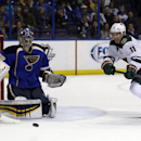 Minnesota Wild's Zach Parise, right, chases after a loose puck as St. Louis Blues goalie Ryan Miller defends during the first period of an NHL hockey game Thursday, March 27, 2014, in St. Louis The Associated Press