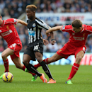 Newcastle United's Rolando Aarons, center, vies for the ball with Liverpool's Joe Allen, left, and captain Steven Gerrard, right, during their English Premier League soccer match at St James' Park, Newcastle, England, Saturday, Nov. 1, 2014